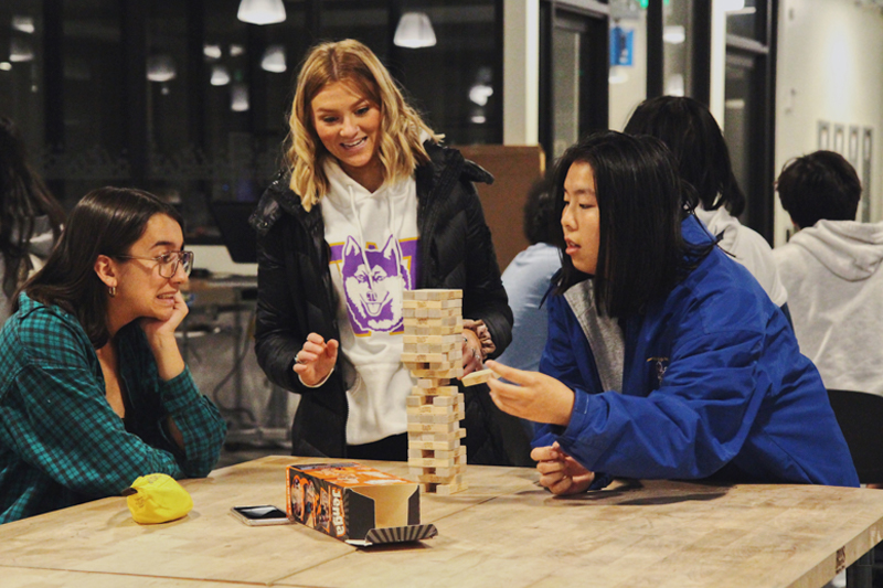 Students playing Jenga in their residence hall floor lounge